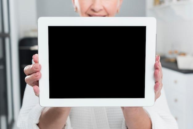 Ältere aufwerfende frau beim halten der tablette
