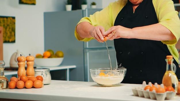 Ältere bäckerfrau knackt eier auf glasschüssel für leckeres essensrezept in der heimischen küche. pensionierter älterer koch mit bonete, der von hand mischt und gebäckzutaten knetet, die hausgemachten kuchen backen.