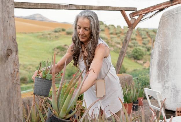 Ältere bäuerin, die ihre pflanzen gießt