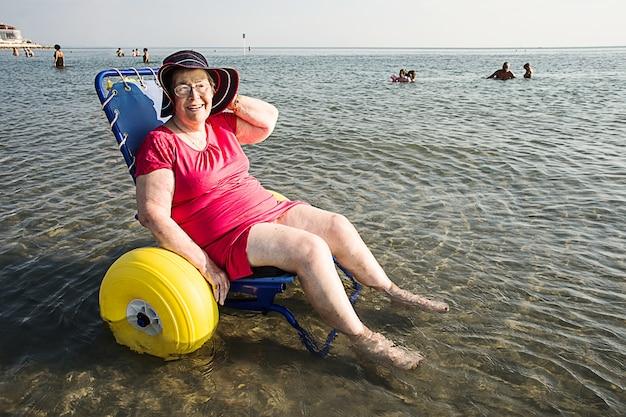 Ältere behinderte dame im rollstuhl zum strand