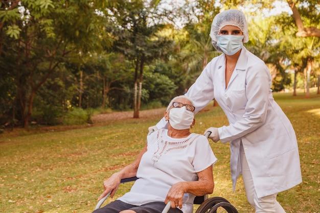 Ältere behinderte frau mit betreuerin im garten des pflegeheims