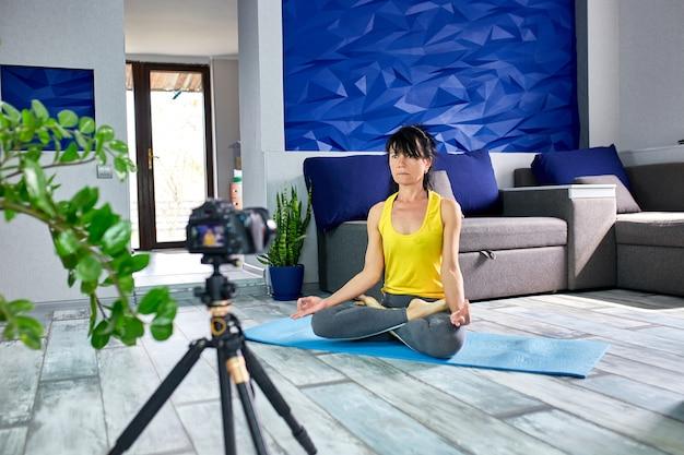 Ältere bloggerin mit schlanker körperform in sportbekleidung, die zu hause yoga macht.