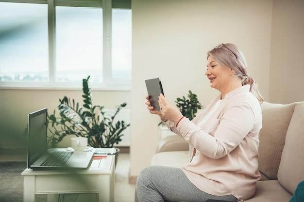 Ältere blonde geschäftsfrau mit brille, die eine videokonferenz auf tablette beim sitzen auf sofa mit einem laptop hat