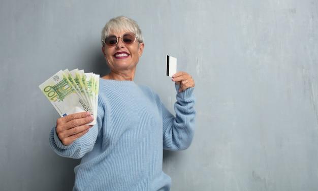 Ältere coole frau mit einer kreditkarte gegen schmutzzementwand.