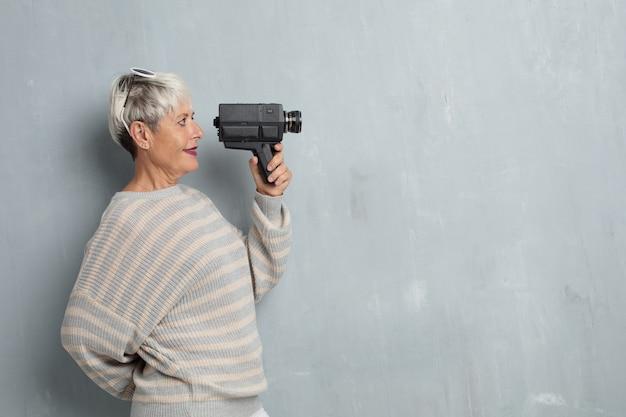Ältere coole frau mit einer vinatge videokamera gegen schmutz cem