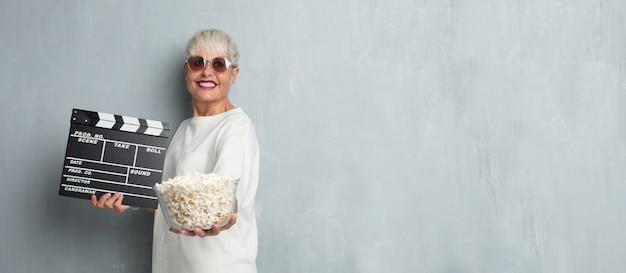 Ältere coole frau mit pop corns gegen schmutzzementwand. cin