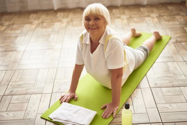Ältere dame cobra asana, die zu hause yoga übt.