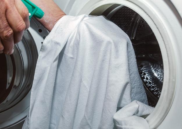 Ältere dame desinfiziert ein weißes tuch mit einem grünen spray, das ein desinfektionsmittel enthält, bevor sie es in die waschmaschine steckt