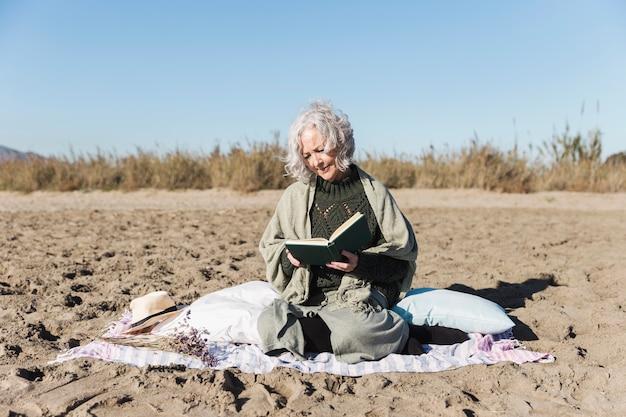 Ältere dame, die buch draußen liest