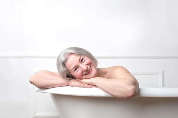 Ältere dame, die ein bad genießt