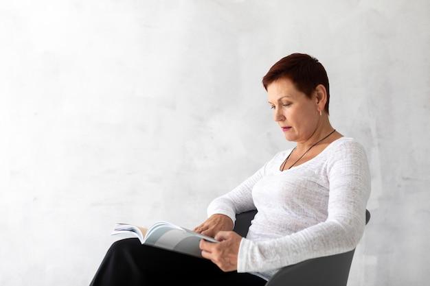Ältere dame, die eine zeitschrift liest