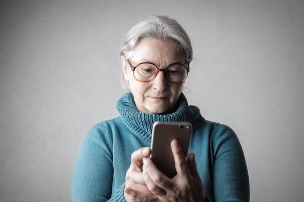 Ältere dame, die einen smartphone verwendet