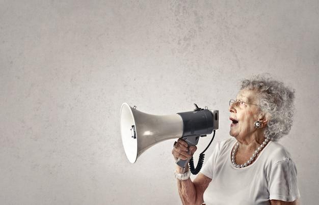 Ältere dame, die in ein megaphon spricht