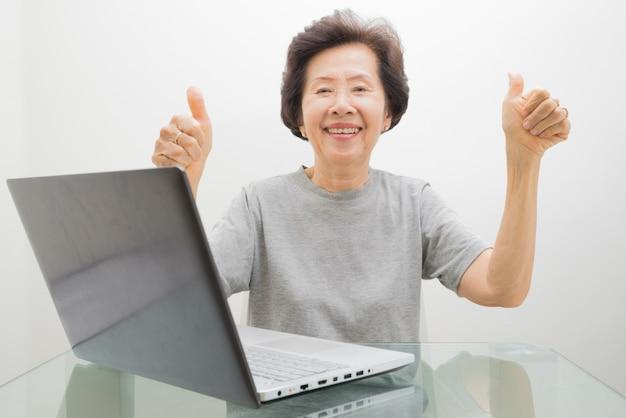 Ältere dame, die mit laptop, mit laptop und den daumen oben arbeitend arbeitet