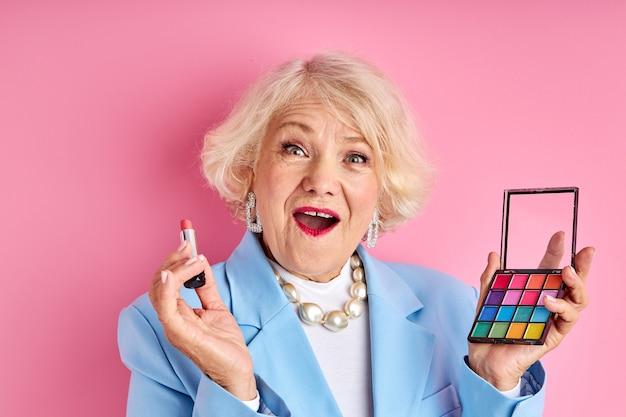 Ältere dame, die neue produktkosmetik lokalisiert auf rosa raum, schönheitskonzept anwendet