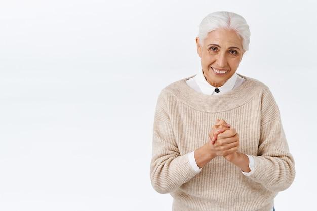 Ältere dame im büro, die sich herzlich für ihr kommen bedankt, sich höflich verbeugt, die hände dankbar für die einladung zusammendrückt, zufrieden lächelt, ein gutes geschäft unterschrieben hat, die weiße wand zufrieden steht