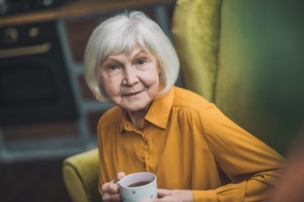 Ältere dame in gelb, die in ihrer küche sitzt