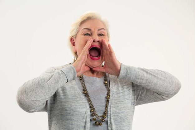 Ältere dame schreit frau händchen haltend in der nähe von mund