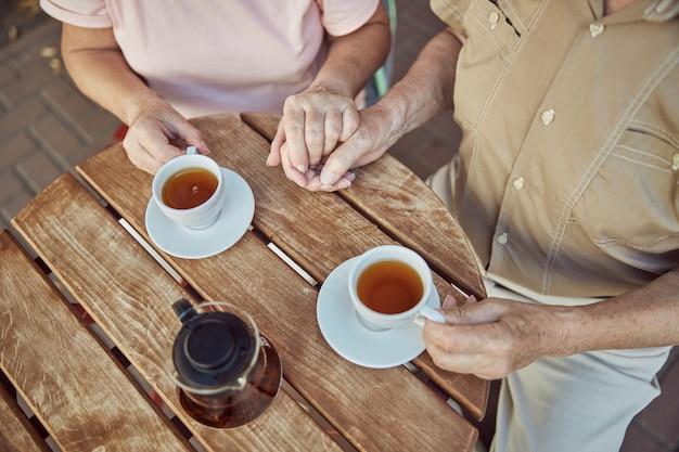Ältere dame und ein kaukasischer mann in einem poloshirt, die händchen halten Premium Fotos