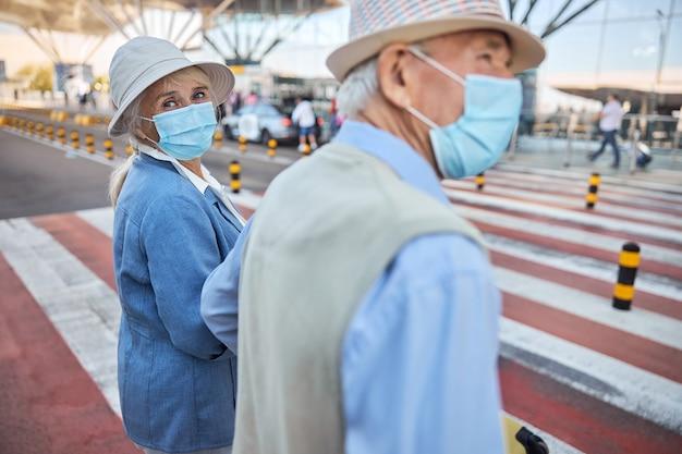 Ältere dame und ihr ehepartner in gesichtsmasken stehen mit ihrem gepäck am fußgängerüberweg