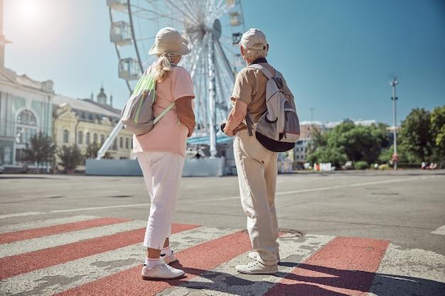 Ältere dame und ihr grauhaariger ehepartner beim blick auf das riesenrad
