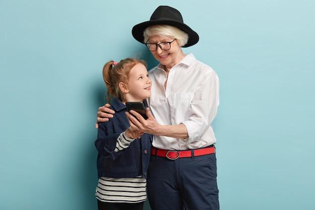 Ältere dame und kleines süßes mädchen verwenden mobiles foto, um fotos anzusehen, nachrichten zu senden, sich mit liebe zu umarmen, freizeit zusammen zu verbringen. kleines kind bringt oma bei, wie man handy benutzt.
