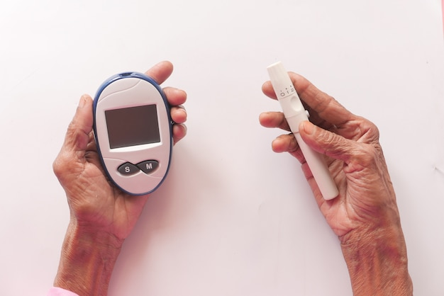 Ältere diabetikerinnen messen zu hause den glukosespiegel