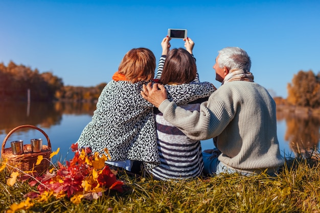 Ältere eltern, die selfie durch herbstsee mit ihren erwachsenen tochter familienwerten nehmen