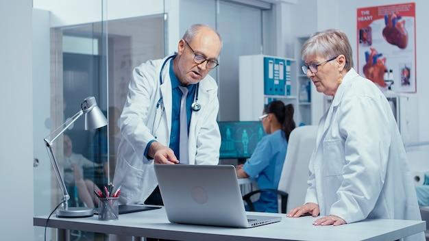 Ältere erfahrene ärzte beraten sich gegenseitig in einer modernen privatklinik mit glaswänden. senior authentische ärzte in modernen privaten krankenhauskliniken medizin und behandlung des gesundheitssystems