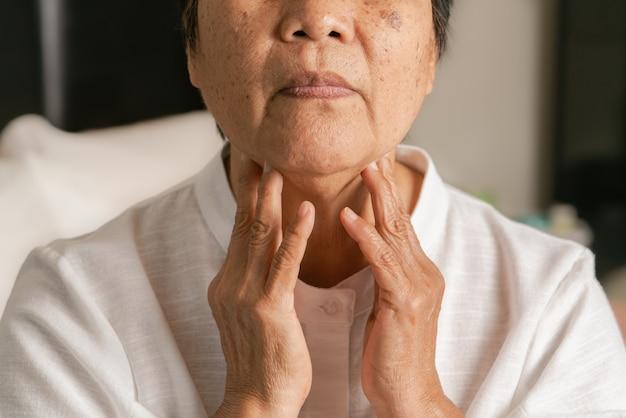 Ältere erwachsene frauen, die den nacken berühren, fühlen sich unwohl husten mit halsschmerzen. gesundheits- und medizinkonzept