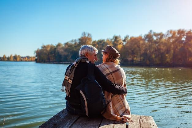 Ältere familienpaare, die durch herbstfluß sich entspannen. glücklicher mann und frau, die natur genießt und das sitzen auf pier umarmt