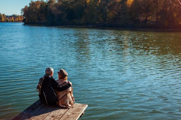 Ältere familienpaare, die durch herbstsee sich entspannen. glücklicher mann und frau, die natur genießt und das sitzen auf pier umarmt