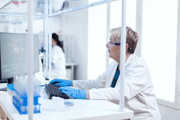 Ältere forscherin, die an einem computer arbeitet, der an ihrem arbeitsplatz sitzt. leitender wissenschaftler im pharmazeutischen labor, der genetische forschung mit laborkittel mit team im hintergrund durchführt.
