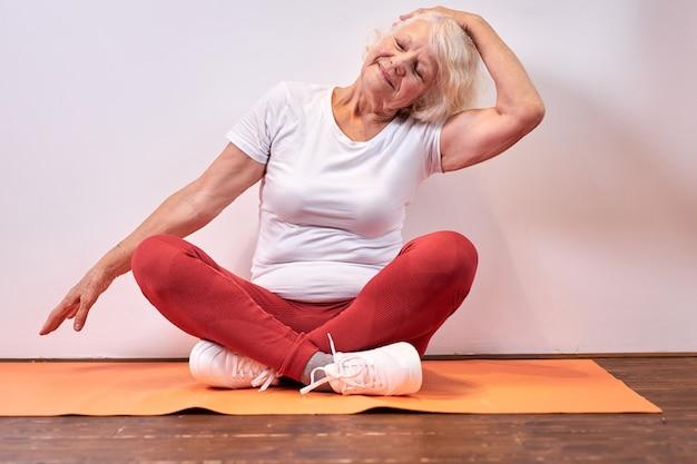Ältere frau 60 jahre alt sitzt sport-, erholungs- und sportkonzept, wohlbefinden