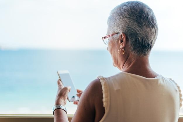 Ältere frau am handy zu hause