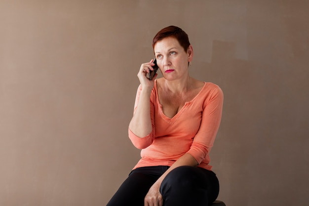 Ältere frau an der vorderansicht des telefons