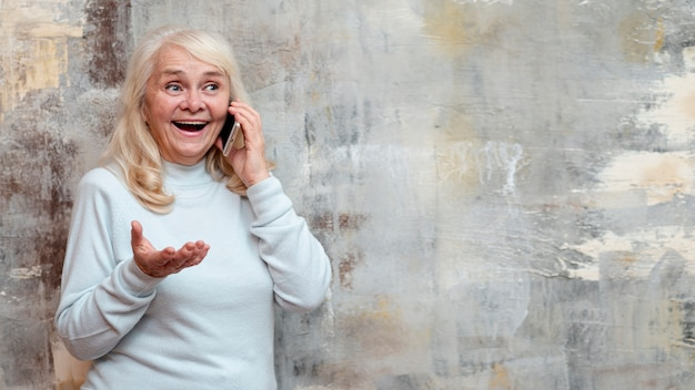 Ältere frau an gefrorenem fenster sprechend über telefon