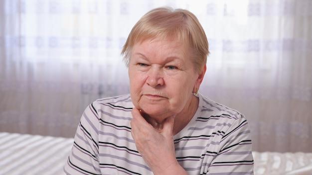 Ältere frau auf dem bett mit halsschmerzen.