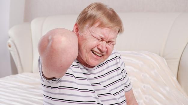 Ältere frau auf dem bett mit nackenschmerzen.
