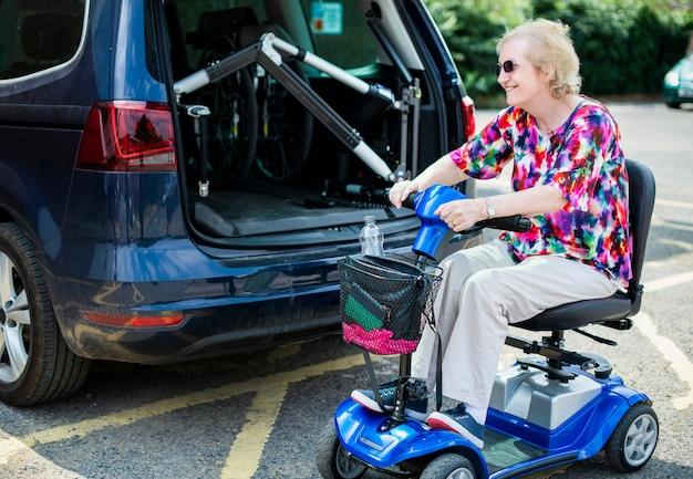 Ältere frau auf einem elektrischen rollstuhl