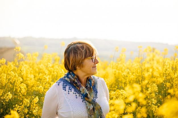 Ältere frau auf einem gebiet der gelben blumen