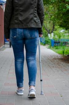 Ältere frau auf einer rehabilitation nach chirurgie oder auf wiederaufnahme geht mit gehendem stock draußen.