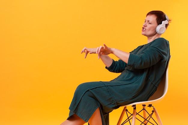 Ältere frau auf hörender musik und tanzen des stuhls