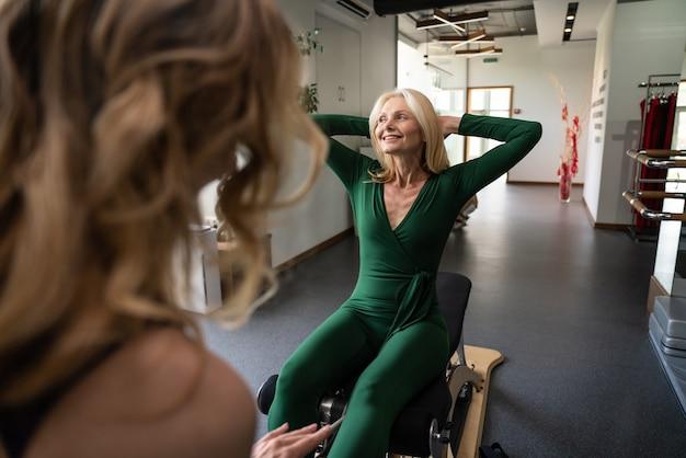 Ältere frau bei körperlicher rehabilitation und pilates mit ihrem trainer im sportzentrum