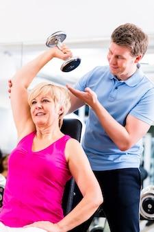 Ältere frau bei sportübung im fitnessstudio mit trainer