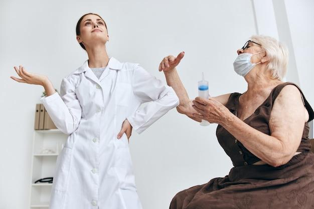 Ältere frau beim arzttermin injektion in den armimpfpass
