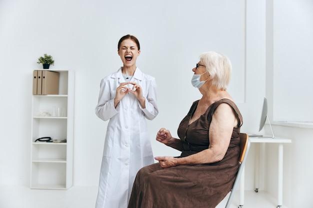 Ältere frau beim arzttermin injektion ins armkrankenhaus