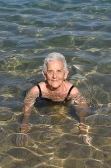 Ältere frau beim baden im meer,