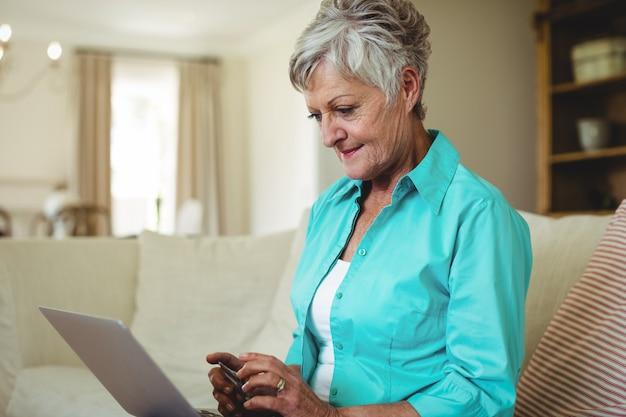 Ältere frau beim online-shopping auf dem laptop