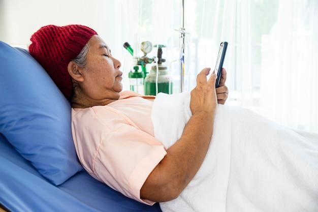 Ältere frau benutzte smartphone auf patientenbett im krankenhaus